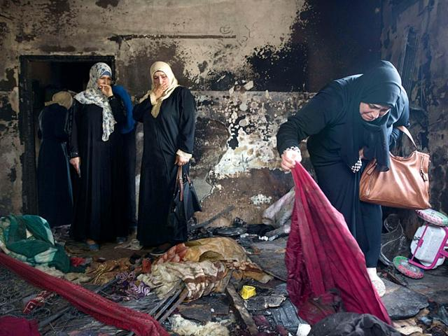Palestinian women look at the damage at the Dawabsha family's home in the West Bank village of Duma. Israel on Sunday indicted two extremists with the murder of Dawabsha couple and their child.