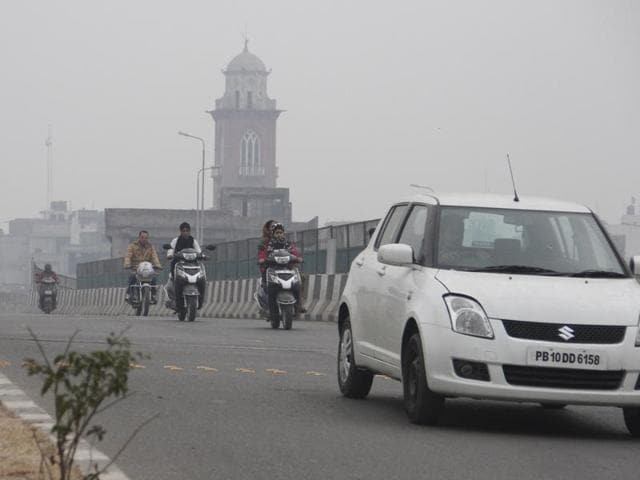 Commuters moving ahead in foggy conditions in Ludhiana on Monday.