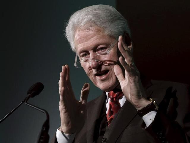 Former President Bill Clinton listens to his wife, Democratic presidential candidate Hillary Clinton, speak in Ames, Iowa, on November 15, 2015.