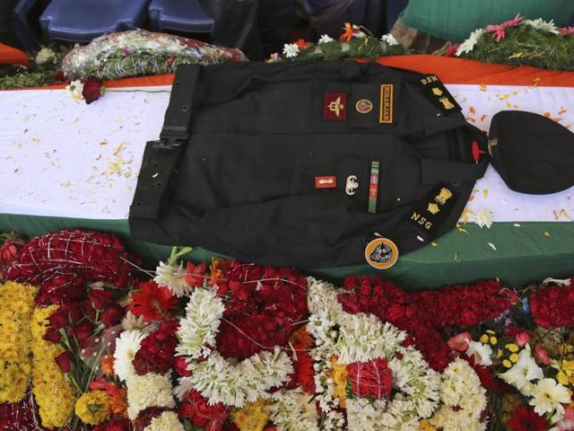 The uniform of National Security Guard commando Niranjan Kumar, who was among those killed in the attack on the Pathankot air force base is placed on his coffin draped in an Indian flag, in Bangalore.
