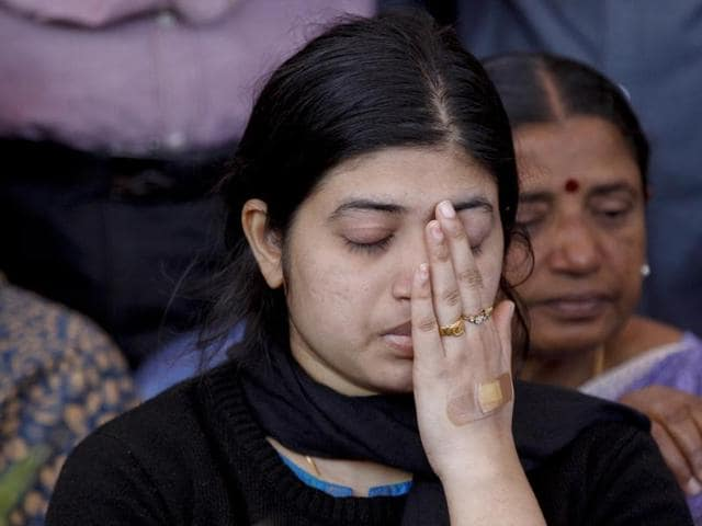 Wife Radhika, wipes her face as she sits next to the coffin of her husband and India