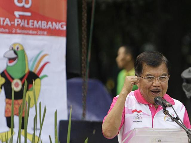 Indonesian Vice President Jusuf Kalla delivers his speech as banners with Asian Games mascot, called Drawa, stand in the background in Jakarta, Indonesia.
