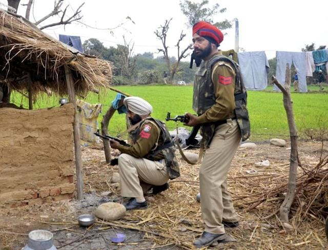 Punjab Police officers conduct a search operation at Manwal village in Pathankot during anti-terrorist operations on Monday.
