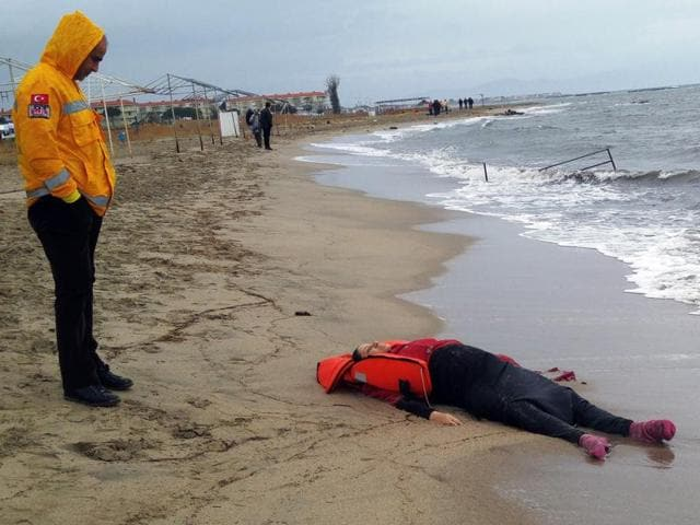 A Turkish rescuer looks at the body of a migrant lying on the beach in Ayvalik, Turkey on Tuesday. Many  migrants' bodies, including of some children, were washed ashore Turkey in the latest tragedy of boat capsizing in the Aegean sea.