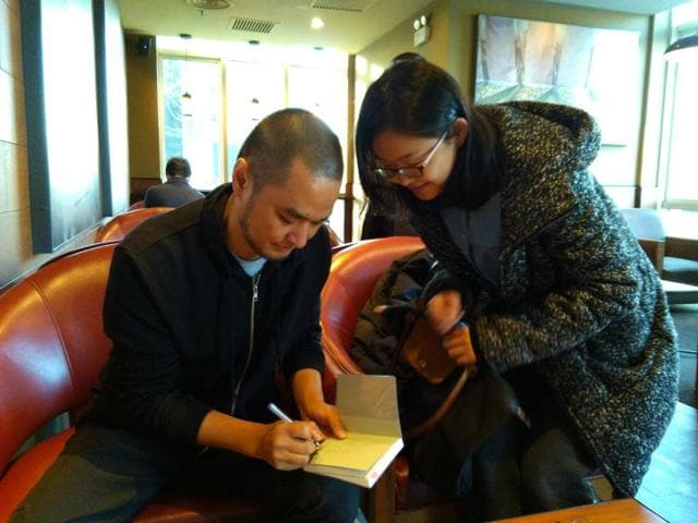 Feng Tang, signing an autograph at a coffee shop.