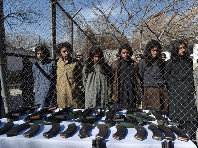 Pakistani Taliban fighters stand with their seized weapons as they are presented to the media in Kabul on January 5, 2016.