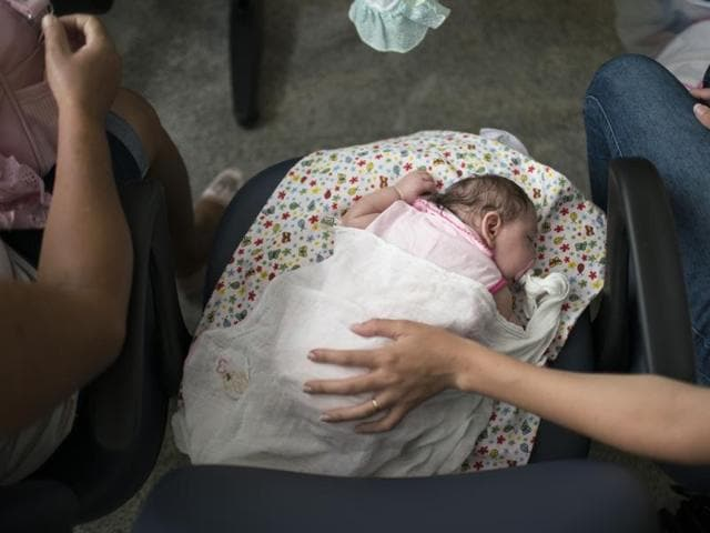 Angelica Pereira, right, holds her daughter Luiza as she waits for their appointment with a neurologist at the Mestre Vitalino Hospital in Caruaru, Pernambuco state, Brazil.