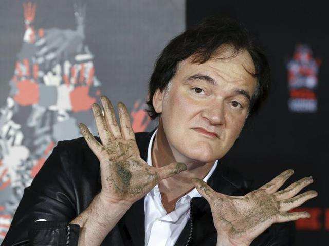 Director Quentin Tarantino poses after placing his handprints in cement in the forecourt of the TCL Chinese theatre in Hollywood, California.