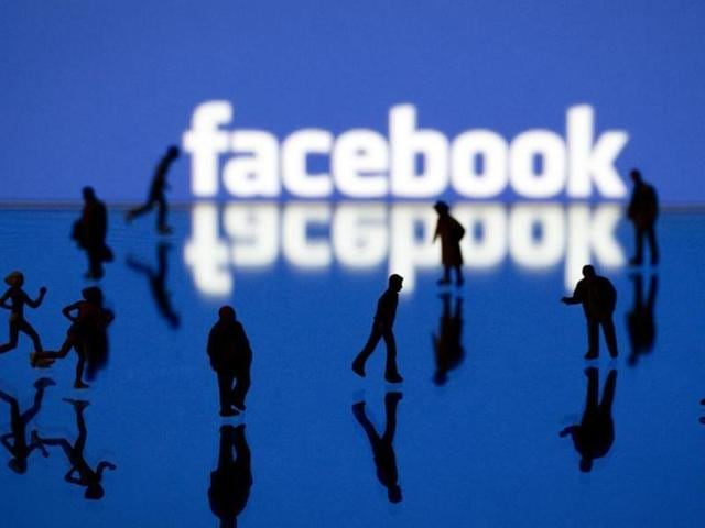 Picture taken in Paris shows an illustration made with figurines set up in front of Facebook's homepage.