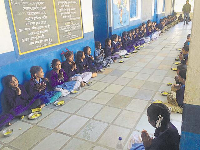 Students pray before having lunch at a government school in Udaipur.