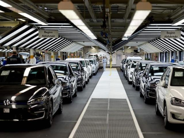(FILES) This file photo taken on October 21, 2015 shows employees of German car maker Volkswagen check cars at a assembly line of the VW plant in Wolfsburg, central Germany.