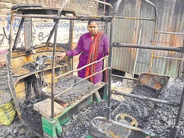 Ruby Singhal looks at the charred remains of her autorickshaw after the fire on Tuesday night.