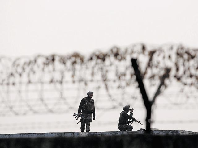 Soldiers keep guard at the perimeter fence of the Indian air force base in Pathankot.