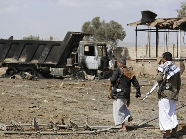 Shia fighters, known as Houthis, inspect the site of Saudi-led airstrikes in Sanaa, Yemen.