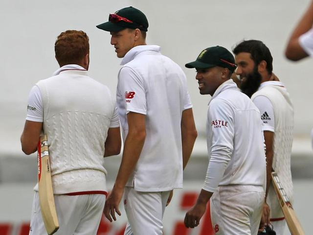 England and South Africa players walk off the pitch after their second Test match was stopped due to rain and bad light, ending in a draw, in Cape Town on January 6, 2016.