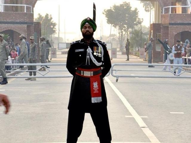 Abhijeet Singh, the first Sikh Pakistan Ranger to be part of the Wagah Border forces, stands at attention