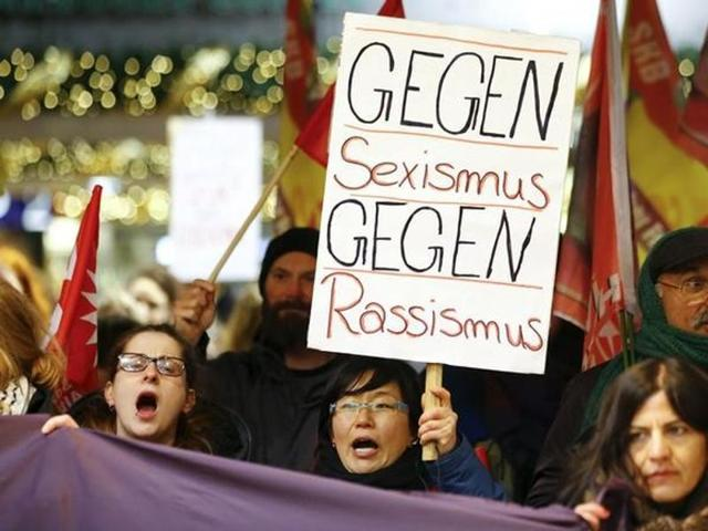 Women shout slogans and hold up a placard that reads 'Against Sexism - Against Racism' as they march through the main railway station of Cologne, Germany.