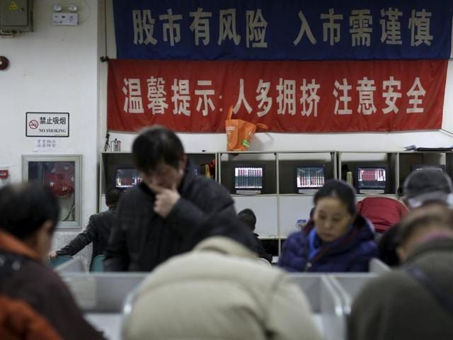 An investor looks at a screen showing stock information at a brokerage house in Shanghai, China, January 8, 2016. China's major stock indexes opened higher on Friday after Beijing ditched a circuit breaker mechanism that halted trading twice this week when share prices tumbled and had been blamed for exacerbating the market sell-offs.