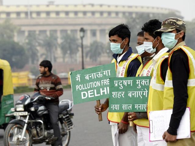 Civil Defence personnel hold placards promoting awareness about the Odd-Even vehicle rationing plan in front of the Parliament House in New Delhi on Wednesday.