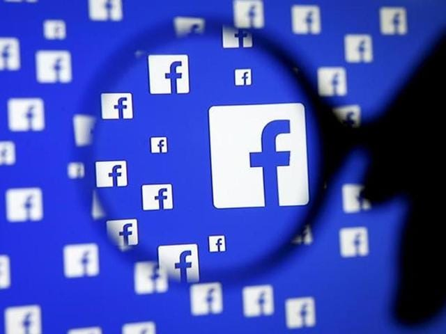 A man poses with a magnifier in front of a Facebook logo on display in this illustration taken in Sarajevo.