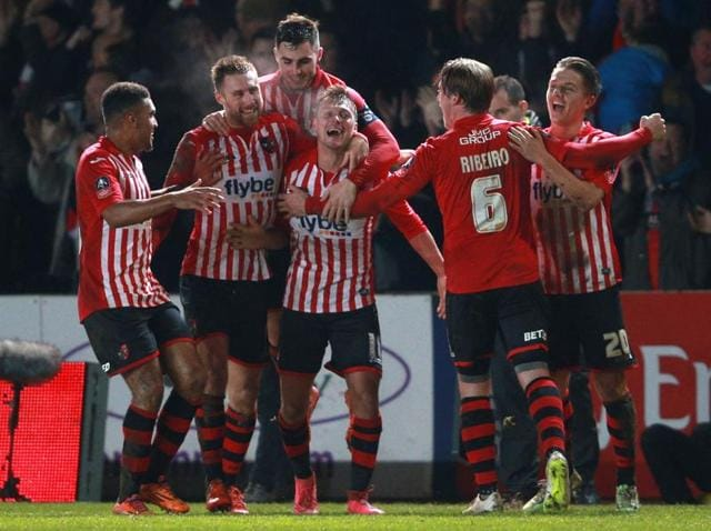 Exeter City's Lee Holmes celebrates scoring against Liverpool with teammates during the English FA Cup.