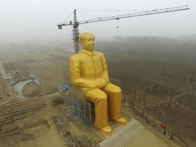 A crane is seen next to a giant statue of Chinese late chairman Mao Zedong under construction near crop fields in a village in Henan province. The 36.6-metre-high golden statue built by several entrepreneurs' contribution worth nearly 3 million yuan ($460,000)  was reportedly demolished following criticism.