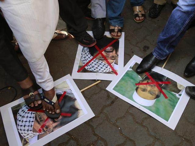 Protestors stamp placards with pictures of Pakistani militant leader Masood Azhar, left and Jamaat-ud-Daawah chief Hafiz Muhammad Saeed as they condemn the attack on the Pathankot air force base in Mumbai.
