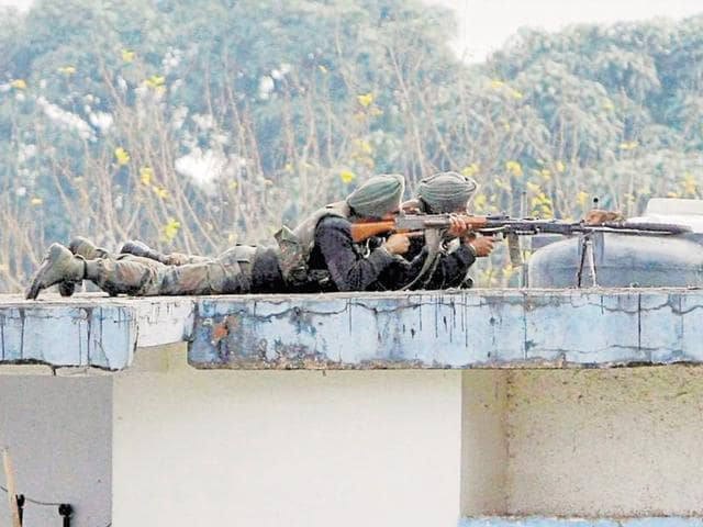 Soldiers are seen on the top of a building at the Indian Air Force base in Pathankot, a day after the end of military operations against terrorists.