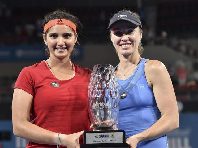 Sania Mirza and teammate Martina Hingis pose with the winning trophy after defeating Germany's Angelique Kerber and Andrea Petkovic.