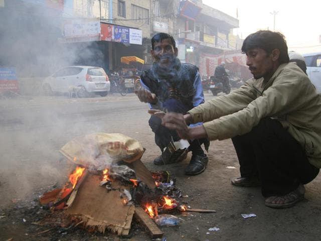 Citizens burn trash bags and woods to gain warmth in New Delhi's Mandawli, while contributing more pollution to environment on Tuesday.