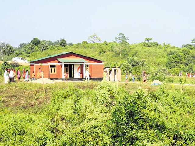 Villagers examine their new homes in New Ram Terang. The first-of-its-kind shift has been a joint effort led by NGOs and the state and local governments.(Subhamoy Bhattacharjee/WTI)