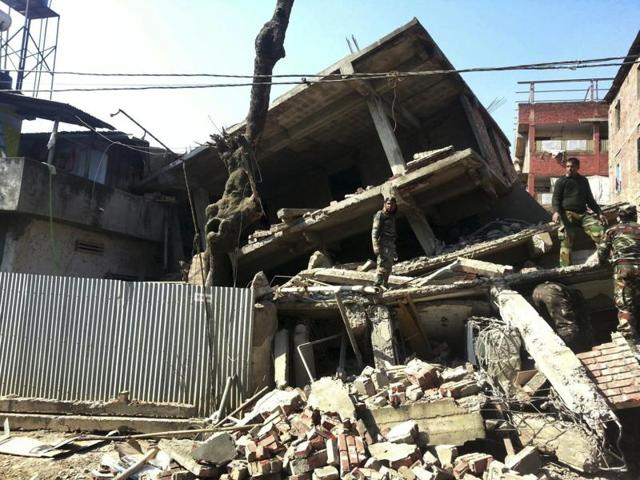 Soldiers inspect a house that collapsed in an earthquake in Imphal, Manipur.