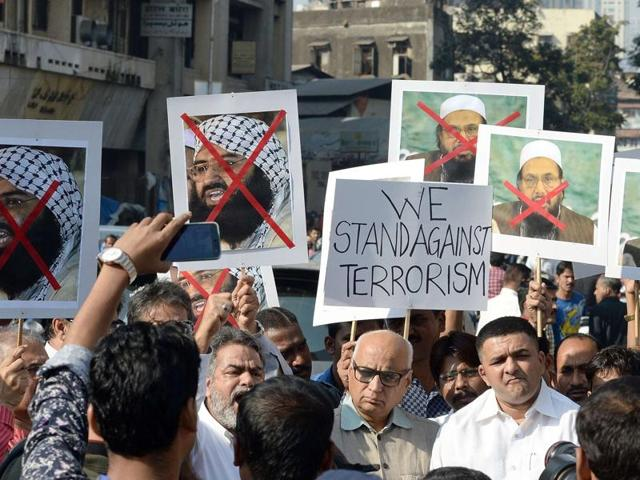 Protesters carry photographs of the chief of Jaish-e-Mohammed and chief of Pakistan's outlawed Islamic hardline Jamaat ud Dawa (JD) during a protest against the attack on the air force base in Pathankot.
