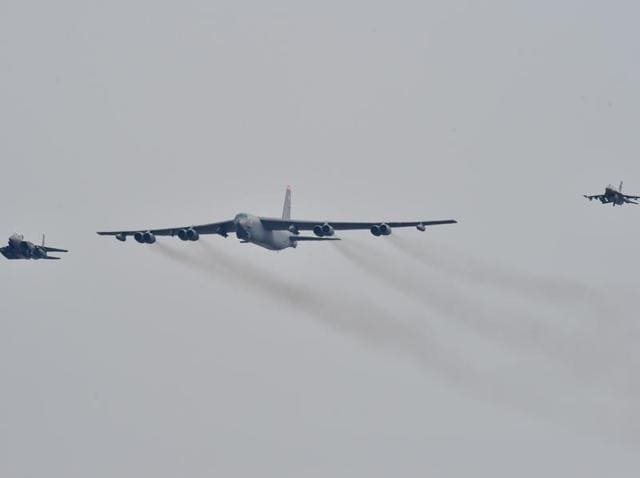 A US B-52 Stratofortress (C) is escorted by a South Korean F-15K fighter jet (L) and a US F-16 fighter jet (R) as it flies over the Osan Air Base in Pyeongtaek.