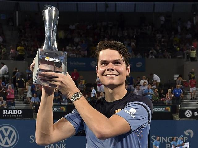 Milos Raonic hits a volley return against Roger Federer during their men's singles final match at the Brisbane International tennis tournament.