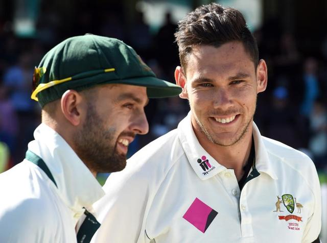 Australian bowler Scott Boland speaks with teammate Nathan Lyon  after Australia defeated the West Indies.