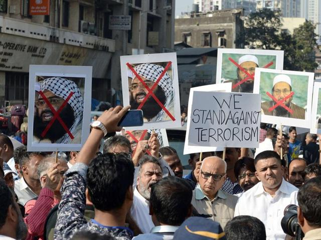 Protesters carry photographs of the chief of Jaish-e-Mohammed, Maulana Masood Azhar (L) and chief of Pakistan's outlawed Islamic hardline Jamaat ud Dawa (JD), Hafiz Mohammad Saeed (R) during a protest against the attack on the air force base in Pathankot.
