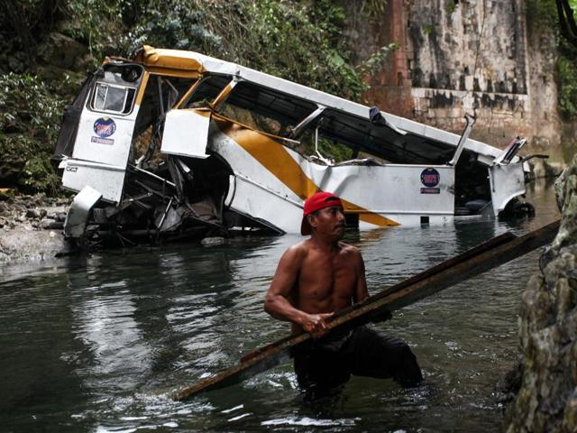 A passenger bus lays in a ravine after falling off the road in Atoyac, Veracruz state, Mexico, Sunday, Jan. 10, 2016. The bus, belonging to the Paso del Toro line, was carrying members of a football team and their relatives along the road connecting the cities of Camaron and Cordoba. According to authorities, at least 20 people were killed and 25 were injured.