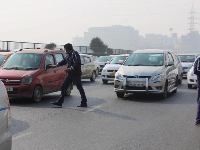 Traffic Police slaps challan to a commuter on Delhi Gurgaon expressway for violating Odd- Even scheme at Gurgaon-Delhi border on Tuesday.