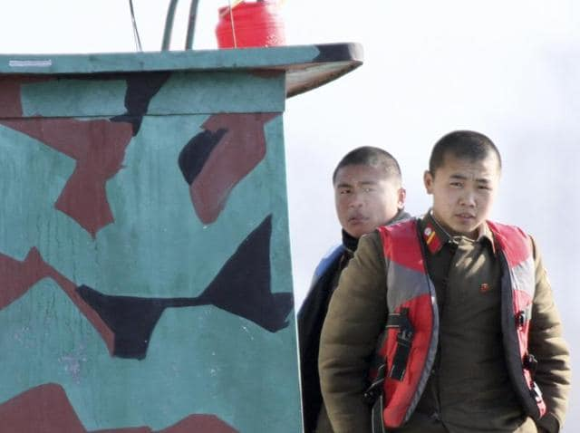 North Korean soldiers look out from a patrol boat on the Yalu River, near the North Korean town of Sinuiju, opposite the Chinese border city of Dandong.