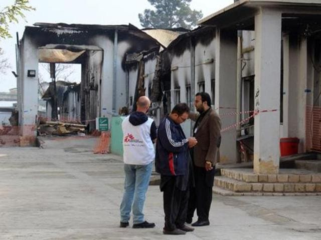 "Staff members gather outside the damaged Medecins Sans Frontieres (MSF) hospital in Afghanistan's city of Kunduz. The US airstrike on the hospital earlier in October 2015 was  ""caused primarily by human error""."