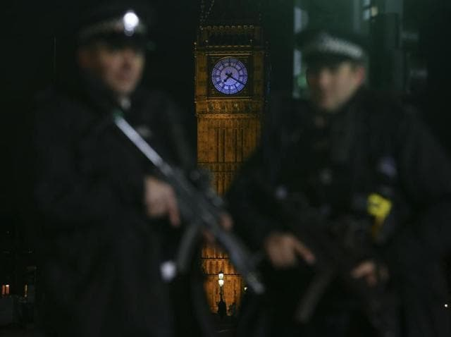 Armed police officer patrol with Elizabeth Tower (Big Ben) in the background ahead of the New Year's Eve fireworks in London on December 31, 2015. British police said they would deploy more armed officers than usual on the streets of London for New Year's Eve, as the terror threat level remains at