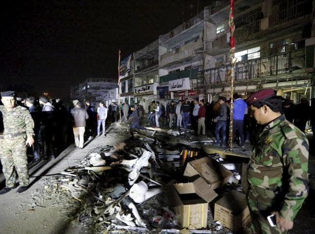 Iraqi security forces gather at the site of a car bomb in New Baghdad on Monday in which at least 12 have been killed.