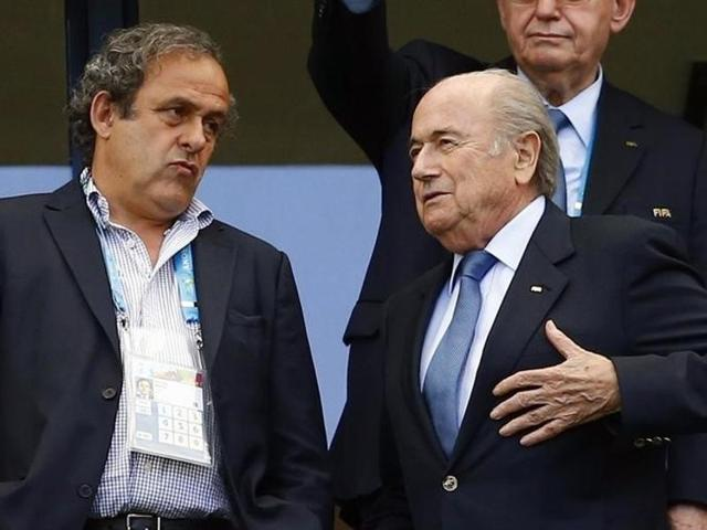 A file photo of former FIFA President Sepp Blatter speaking with suspended UEFA President Michel Platini.