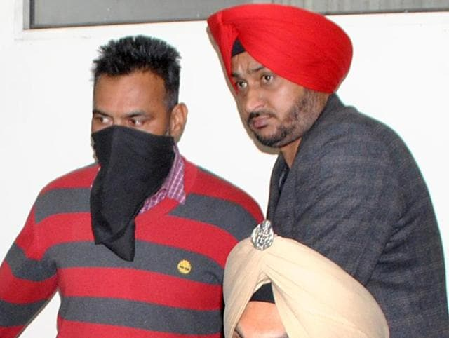 Prem Singh (face covered) was arrested from his native place in Tarn Taran when he was on leave. He was posted as a head constable with the 72 Battalian of BSF in Barmer in Rajasthan.