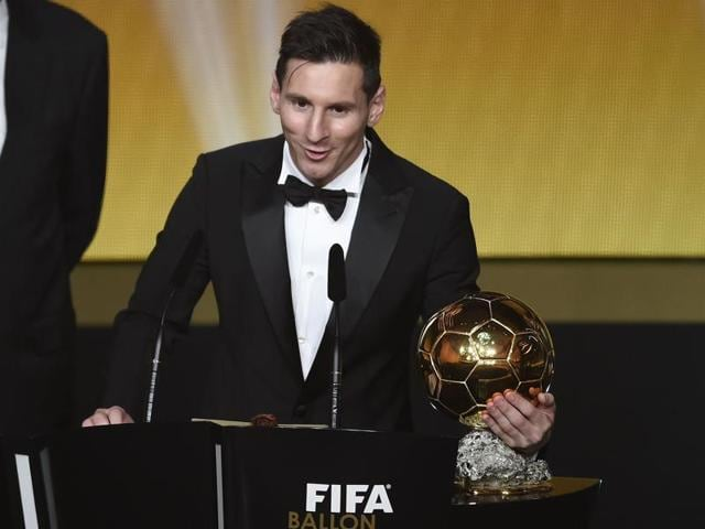 Lonel Messi holds his trophy as he shakes hands with Neymar after receiving the 2015 FIFA Ballon d'Or award.