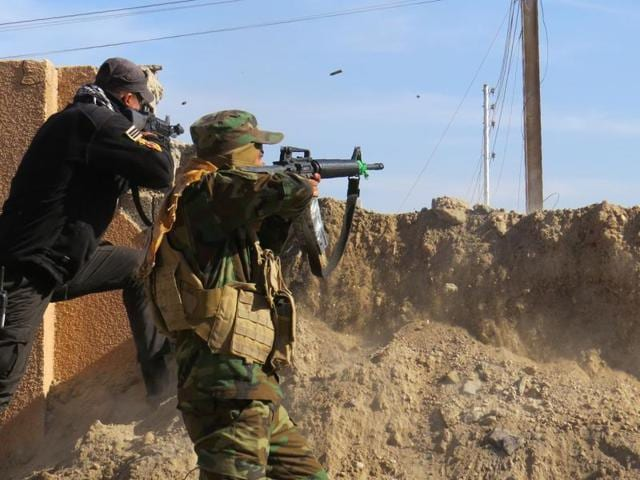 Members of the Iraqi forces battle with Islamic State group fighters east of Ramadi to take control of parts of the capital of Iraq's Anbar province on Tuesday. Iraqi forces continue to clear the city and evacuate civilians two weeks after declaring victory against the Islamic State group.