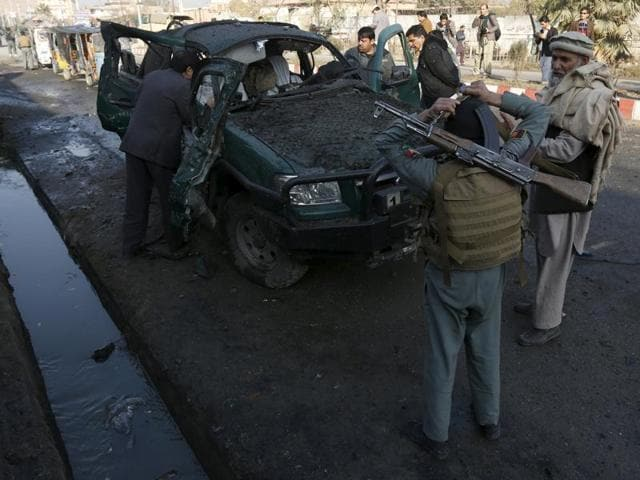 Afghan security personnel stand next to a damaged police vehicle after a blast near the Pakistani consulate in Jalalabad, Afghanistan.