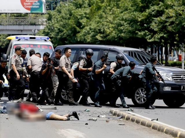 Dead bodies are seen as Indonesian police hold rifles while walking behind a car for protection.