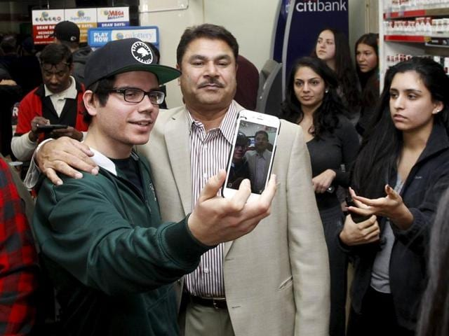 Rod Lomeli (L) takes a selfie with Balbir Atwal (C), the owner of the 7-Eleven store where a winning Powerball ticket was sold.